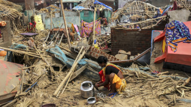A woman prepares food in the Puri district of Odisha amid the destruction left by Cyclone Puri.