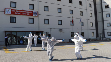 Turkish health officials perform an impromptu dance to celebrate the end of quarantine for health workers returning  from Kazakhstan and Russia.