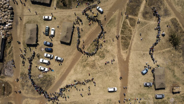 People wait in queues to cast their vote at a polling station in Harare.