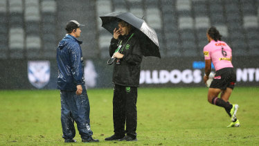Ground staff speaks to an NRL official as they stand in heavy rain at Bankwest Stadium on Saturday afternoon.