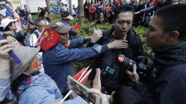 A pro-Beijing supporter yells and pushes a photographer during a rally in Hong Kong on December 7.