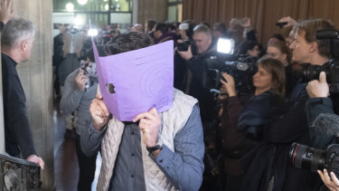 A defendant covers his face when arriving at the court in Berlin, Germany.