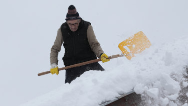 A man shovels snow from the roof of his house in a remote village near Kladanj, 80 kms north of Sarajevo, Bosnia, on Friday.
