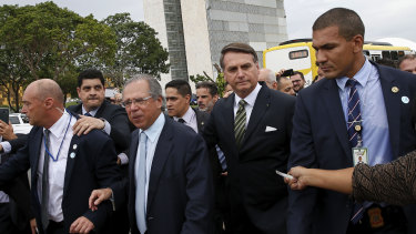 President Jair Bolsonaro, centre right, and Economy Minister Paulo Guedes, centre left, walk back to the presidential palace after a meeting.