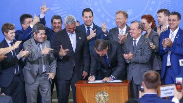 Brazilian President Jair Bolsonaro signs a decree easing gun laws in Brasilia while lawmakers celebrate.