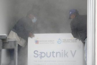Workers place a box containing doses of the Russian COVID-19 vaccine Sputnik V into a refrigerated container after unloading it from a plane, at the Simon Bolivar International Airport in Maiquetia, Venezuela.