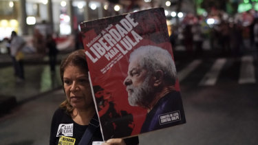 """A woman holds a banner with an image of Brazil's former President Luis Inacio Lula da Silva with the Portuguese message: """"Freedom to Lula,"""" during a protest against government-proposed pension reforms."""