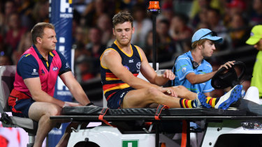 Shattered: Adelaide's Paul Seedsman is taken from the field with a suspected torn ACL.