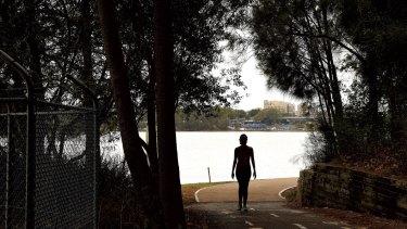 A woman walks along a path on near Leichhardt Oval on The Bay Run.