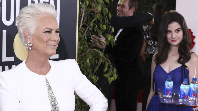 Jamie Lee Curtis is not impressed with Fiji Water Girl, aka Kelleth Cuthbert, photobombing her at the Golden Globe Awards on Sunday in LA.