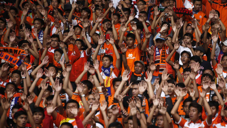 Indonesian soccer fans cheer the home team, Jakarta's Persija. The game is under pressure in the country due to violence off the pitch.