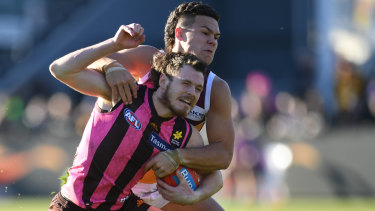 Hawthorn's Blake Hardwick is tackled by young Lion Cameron Rayner.