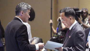 North Korean Foreign Minister Ri Yong Ho, right, receives an envelope from US Ambassador to the Philippines Sung Kim before the start of the 51st ASEAN Foreign Ministers Meeting in Singapore, on Saturday.