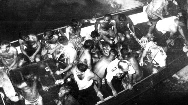 Survivors picked up by naval rescue craft prepare to board the aircraft carrier.