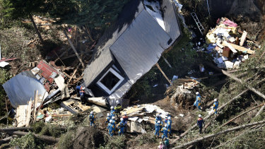 Police search for missing persons around houses destroyed by a landslide.