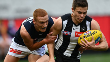 Josh Thomas of the Magpies is tackled by Matthew Cottrell.