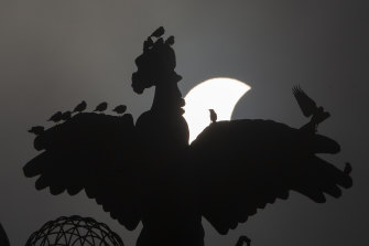A partial solar eclipse moves behind a statue in Islamabad, Pakistan.