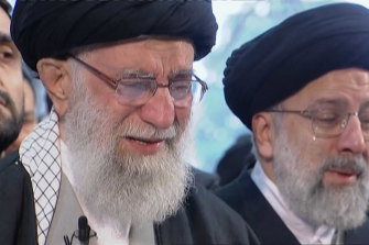 Iranian Supreme Leader Ayatollah Ali Khamenei, left, openly weeps as he leads a prayer over the coffin of Qassem Soleimani.