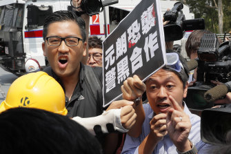 Pro-democracy lawmakers Lam Cheuk-ting, left, and Ted Hui, right, argue with pro-Beijing lawmaker Junius Ho during a demonstration of an anti-riot vehicle equipped in Hong Kong last year.