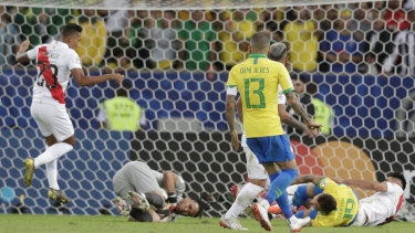 Spot kick: Peru's goalkeeper Pedro Gallese catches the ball as Brazil's Everton, right, is fouled in the penalty area by Carlos Zambrano.