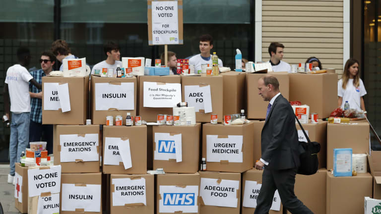 """Anti Brexit activists protest as they deliver a pile of medical supplies in cardboard boxes to the Department of Health and Social Care in London. They want to get a message to the public about the predicted costs of Britain's """"No Deal Hard Brexit""""."""