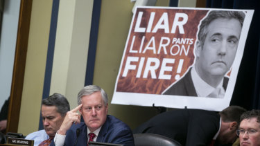 A poster on display during Michael Cohen's testimony to Congress.
