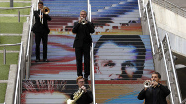 Musicians with the Royal Philharmonic Orchestra play on the Spanish Steps at Wembley Park in London on Saturday.
