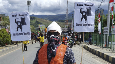 "A protester holds posters that read ""We are monkeys, monkeys want to be separated from Indonesia"", during a rally in Abepura, Papua province, Indonesia."