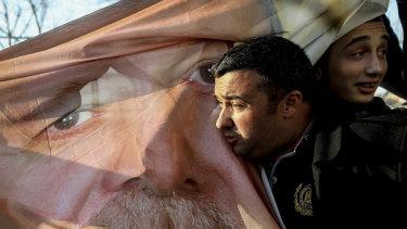 An AKP supporter kisser a banner showing Recep Tayyip Erdogan.