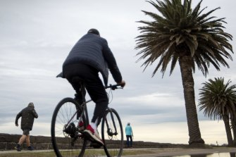 Mind the puddle: people out along Beach Road in Albert Park enjoy the last day of winter.
