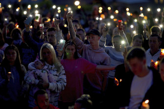 People attend a vigil for the victims of the mass shooting in Plymouth, England on Friday.