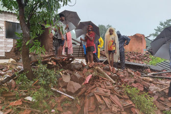People watch rescue efforts after a landslide in Taliye village, in the western Indian state of Maharashtra, Friday, July 23, 2021.