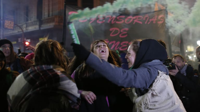 Women in support of decriminalising abortion, one spreading coloured smoke, gather outside Congress in Buenos Aires.