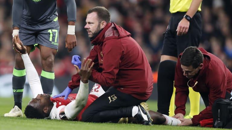 Arsenal's Danny Welbeck receives medical treatment.