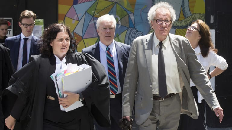 Geoffrey Rush heads into court with his legal counsel on Wednesday.