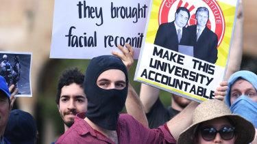 Students hold placards demanding transparency from the University of Queensland.