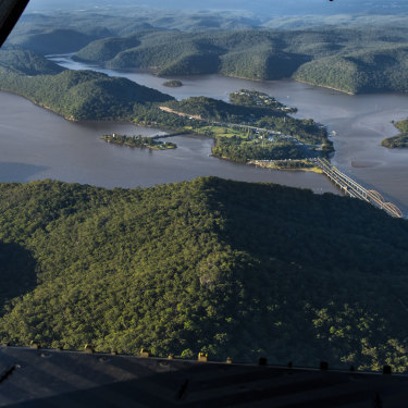 Floodwaters in the Hawkesbury River pass under Hawkesbury River Bridge at Mooney Mooney.