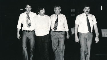 Peter Morgan (second from left) is led away by detectives after his arrest in April 1979. The guy on the far left appears to be wearing a tablecloth as a tie.