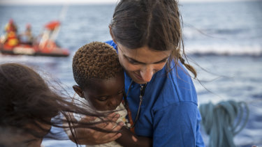 An NGO worker holds a boy at the Mediterranea Saving Humans NGO boat, as they sail off Italy's southernmost island of Lampedusa, just outside Italian territorial waters.