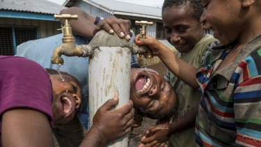 Children enjoying water from a tap in the village of Humbra, Southern Highlands. The restoration of water and sanitation infrastructure was one of the priorities of the UN in the aftermath of the earthquake.