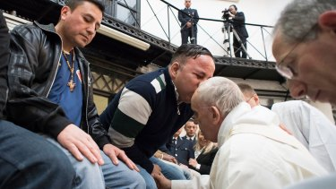 Pope Francis washes the feet of inmates during his visit to the Regina Coeli detention centre in Rome.
