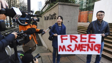 People hold a sign at a Vancouver, British Columbia courthouse prior to the bail hearing for Meng Wanzhou, Huawei's chief financial officer.