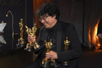 Backstage at the bar, Bong Joon-ho holds the Oscars for best original screenplay, best international feature film, best directing, and best picture for Parasite.