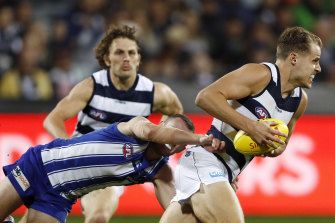 Jake Kolodjashnij of the Cats is tackled by North Melbourne's Jack Mahony during their clash at GMHBA Stadium.