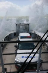 Queensland police vehicle copping a spray from Tropical Cyclone Oma on the way to North Stradbroke Island on Friday.
