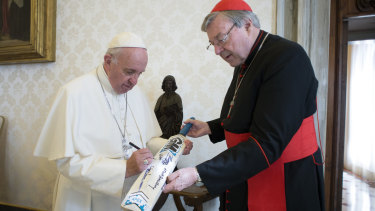Pope Francis signs a cricket bat he received from Cardinal George Pell in 2015.