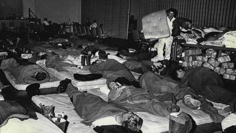 Weary after long hours battling the fires, firefighters stretch out on the floor of the Springwood Civic Centre with tired evacuees. November 30, 1968.