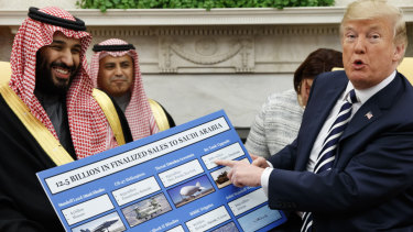 US President Donald Trump holds a chart highlighting arms sales to Saudi Arabia during a meeting with Saudi Crown Prince Mohammed bin Salman in the Oval Office in March.