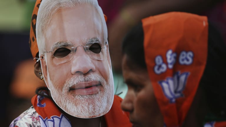 A girl wears a mask of Indian Prime Minister Narendra Modi during an election campaign rally in Bangalore, India.