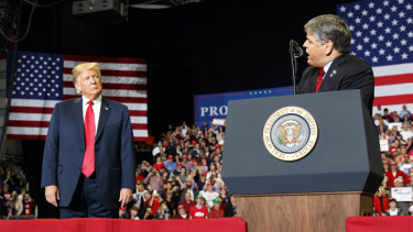 President Donald Trump listens as Fox News' Sean Hannity called the media 'fake news' and said the President kept his promises.